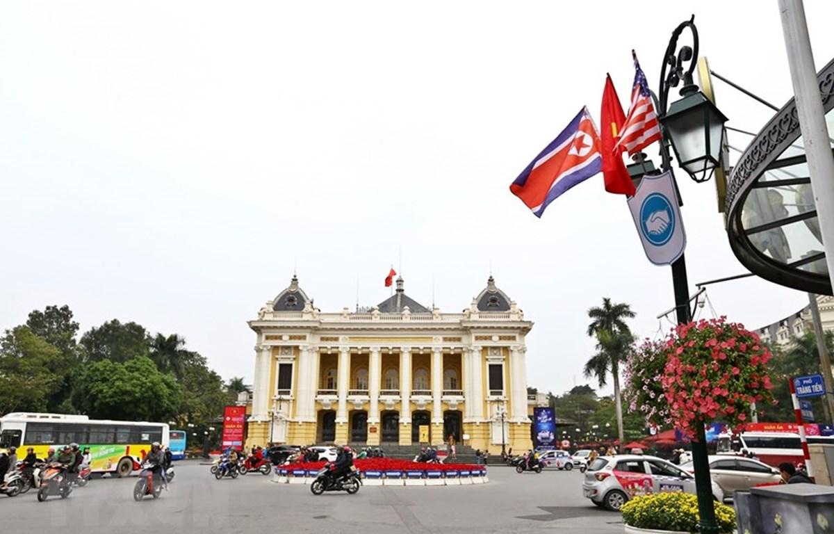 Cờ Mỹ và cờ Triều Tiên, bên dưới là biểu tượng hai bàn tay bắt chặt vào nhau thể hiện tinh thần của cuộc gặp lớn, được treo trên phố Tràng Tiền, trước khu vực Quảng trường 19/8 - Nhà hát Lớn - Khách sạn Hilton Opera, quận Hoàn Kiếm. (Ảnh: Thành Đạt)