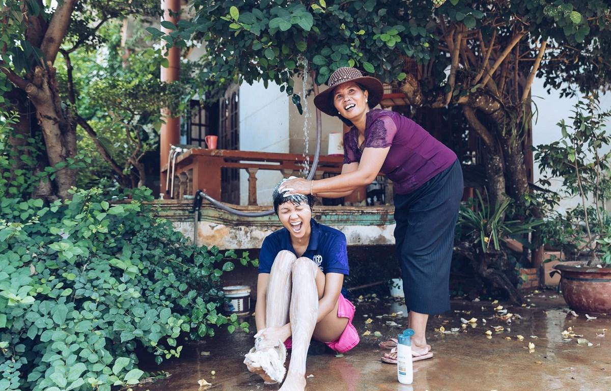 H'Hen Niê hồn nhiên trong khoảnh khắc được trở về tuổi thơ bên mẹ ở quê nhà. (Ảnh: Thiên An/Vietnam+)