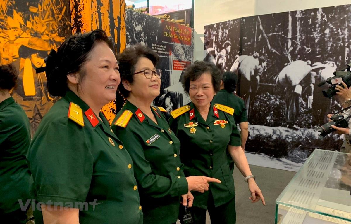 """Những """"cô gái"""" bước ra từ tuyến đường Trường Sơn huyền thoại xúc động ngày gặp lại trong không gian triển lãm 'Kiêu hãnh Trường Sơn' vừa khai mạc sáng nay, tại Bảo tàng Phụ nữ Hà Nội. (Ảnh: Xuân Mai/Vietnam+)"""
