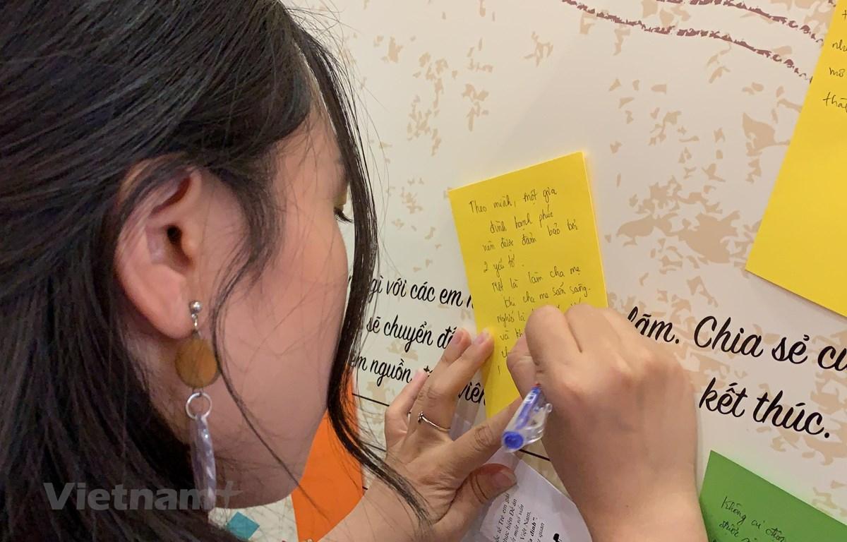 Các em sinh viên cùng những lời nhắn gửi 20 nhân vật chính trong triển lãm. (Ảnh: Xuân Mai/Vietnam+)