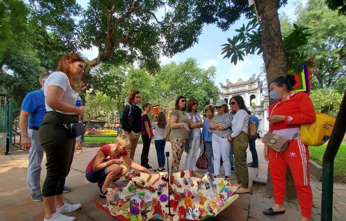 Du khách quốc tế thăm quan Văn Miếu trước thời điểm khu di tích này đóng cửa. (Ảnh: Nguyễn Hoàng/Vietnam+)