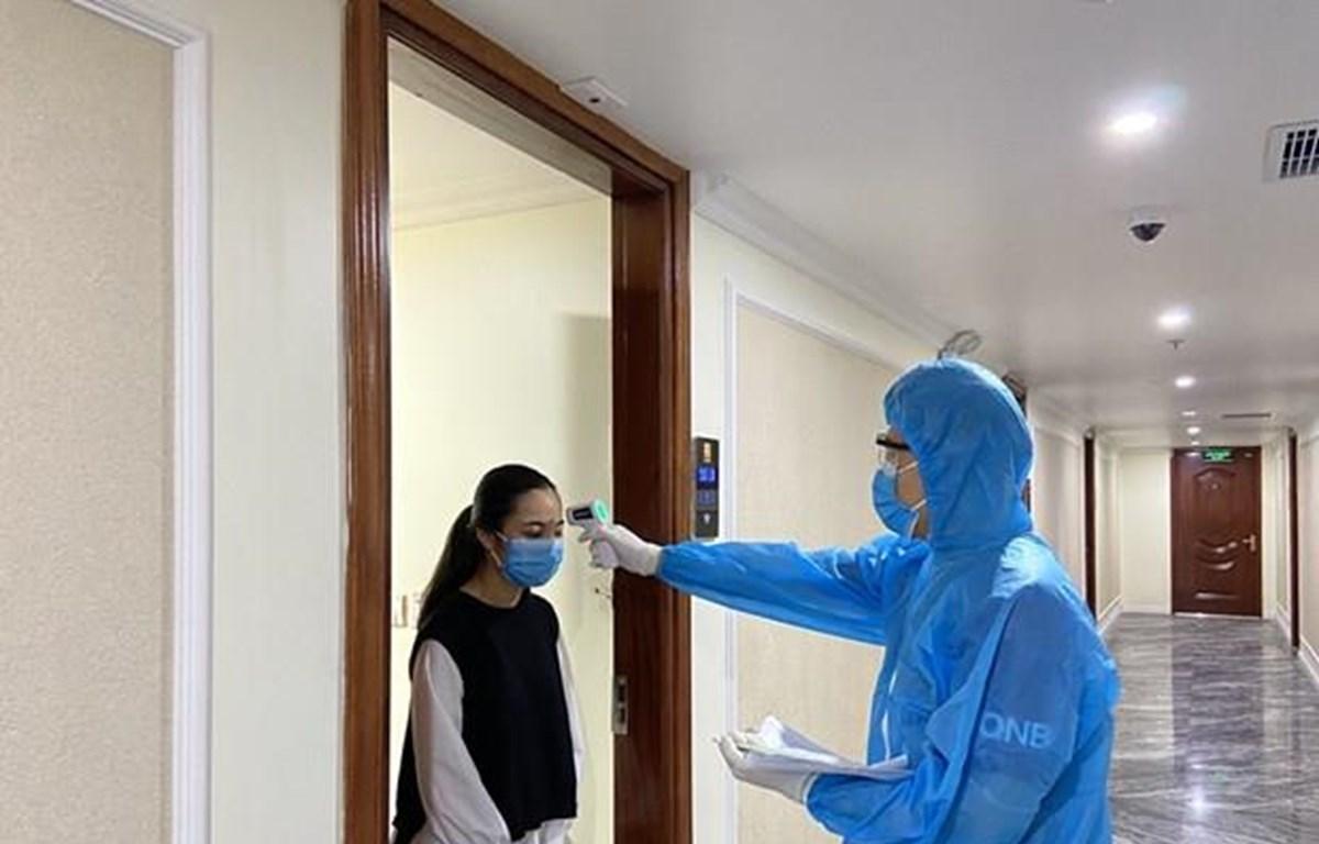 Cán bộ y tế của thành phố Hạ Long kiểm tra thân nhiệt cho khách cách ly y tế tại khách sạn Thái Sơn. (Nguồn: Báo Quảng Ninh)