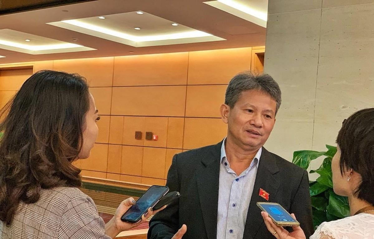 Đại biểu Đỗ Văn Sinh trao đổi với phóng viên bên hành lang Quốc hội. (Ảnh: Xuân Mai/Vietnam+)