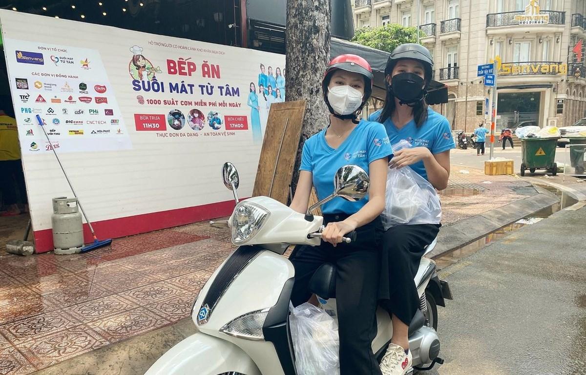 Hoa hậu Tiểu Vy và Á hậu Ngọc Thảo làm 'shipper' đi trao các suất ăn cho lực lượng đầu chống dịch. (Ảnh: CTV/Vietnam+)