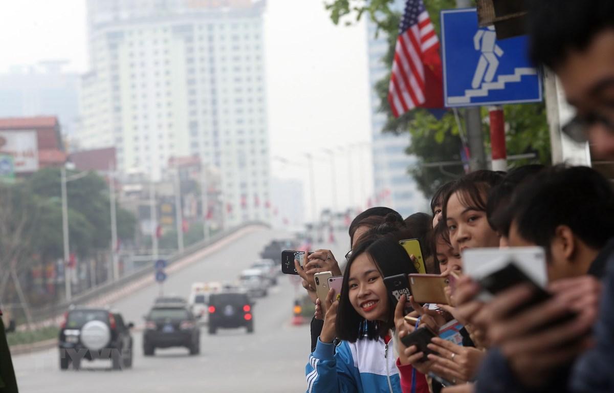 Người dân đứng trên phố Trần Duy Hưng đón đoàn xe của Tổng thống Mỹ Donald Trump đi qua. (Ảnh: Huy Hùng/TTXVN)