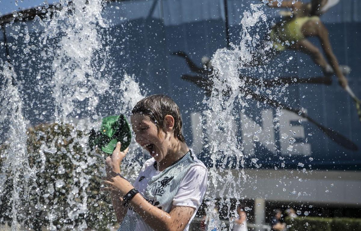 Người dân tránh nóng tại vòi phun nước ở Melbourne, Australia, ngày 24/1/2019. (Ảnh: THX/TTXVN)