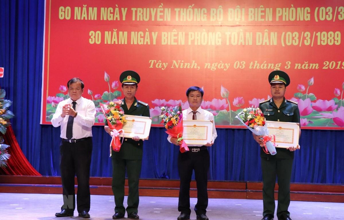 Chủ tịch UBND tỉnh Tây Ninh Phạm Văn Tân tặng bằng khen của Bộ trưởng Bộ Quốc phòng cho 1 tập thể và 2 cá nhân có thành tích đóng góp cho Bộ đội biên phòng. (Ảnh: Lê Đức Hoảnh/TTXVN)