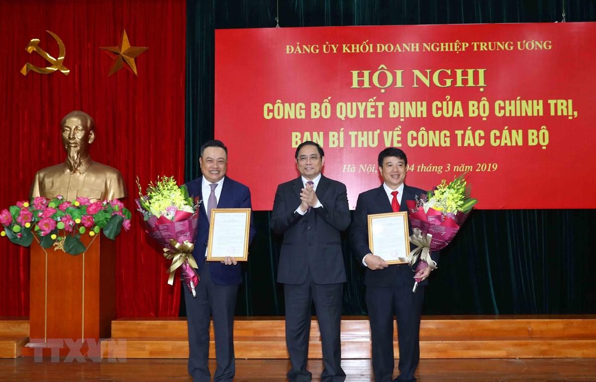 Ông Phạm Minh Chính trao quyết định của Bộ Chính trị cho ông Y Thanh Hà Niê Kđăm (bên phải) và ông Trần Sỹ Thanh (bên trái). (Ảnh: Phương Hoa/TTXVN)