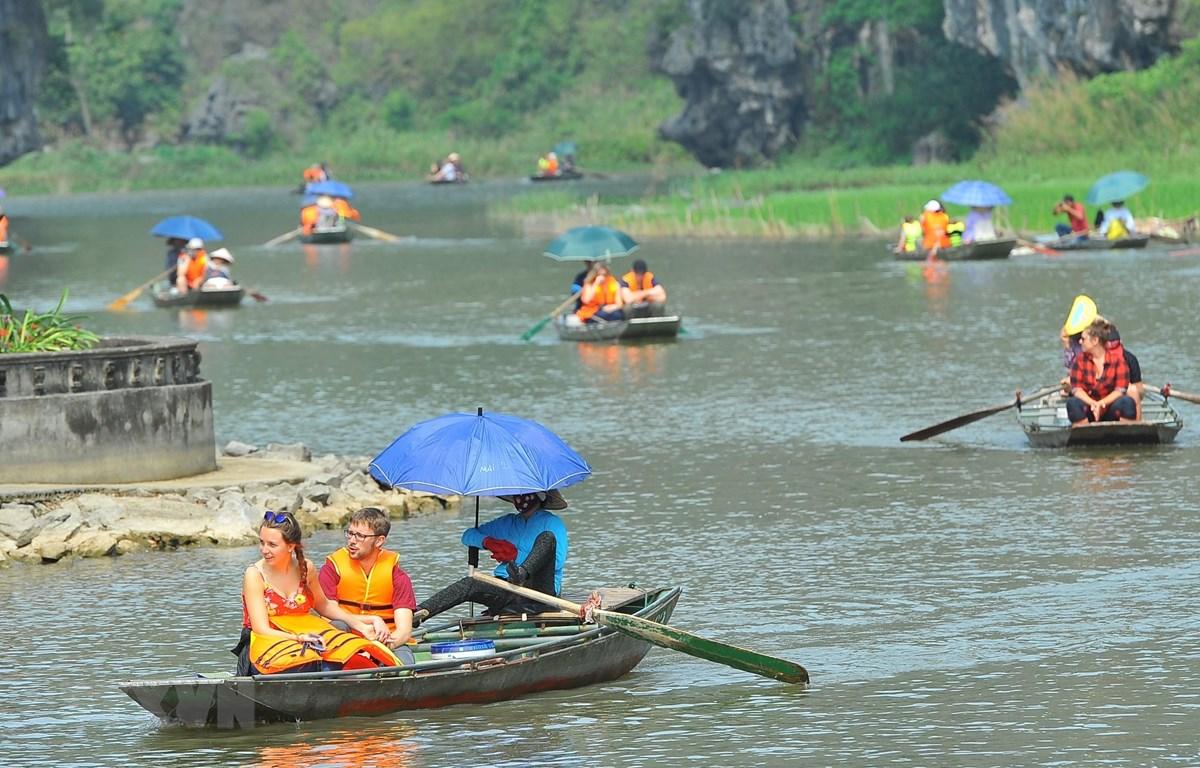 Du khách trong và ngoài nước tham quan khu du lịch Tam Cốc (Ninh Bình) bằng thuyền. (Ảnh: Minh Đức/TTXVN)