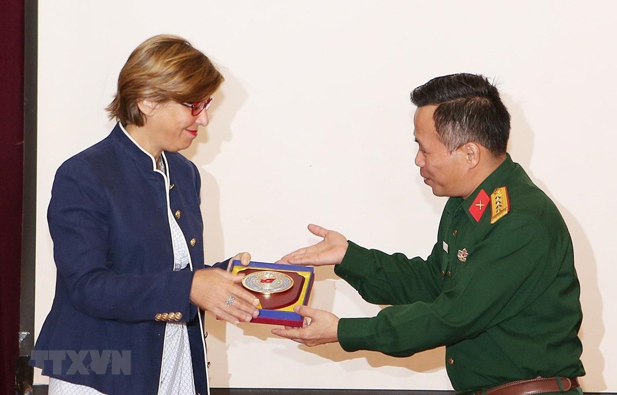 Đại tá Nguyễn Như Cảnh, Phó Cục trưởng Cục Gìn giữ hòa bình Việt Nam tặng quà lưu niệm cho bà Cynthia Petrigh - chuyên gia về Phòng chống bạo lực tình dục của Vương quốc Anh. (Ảnh: Dương Giang/TTXVN)