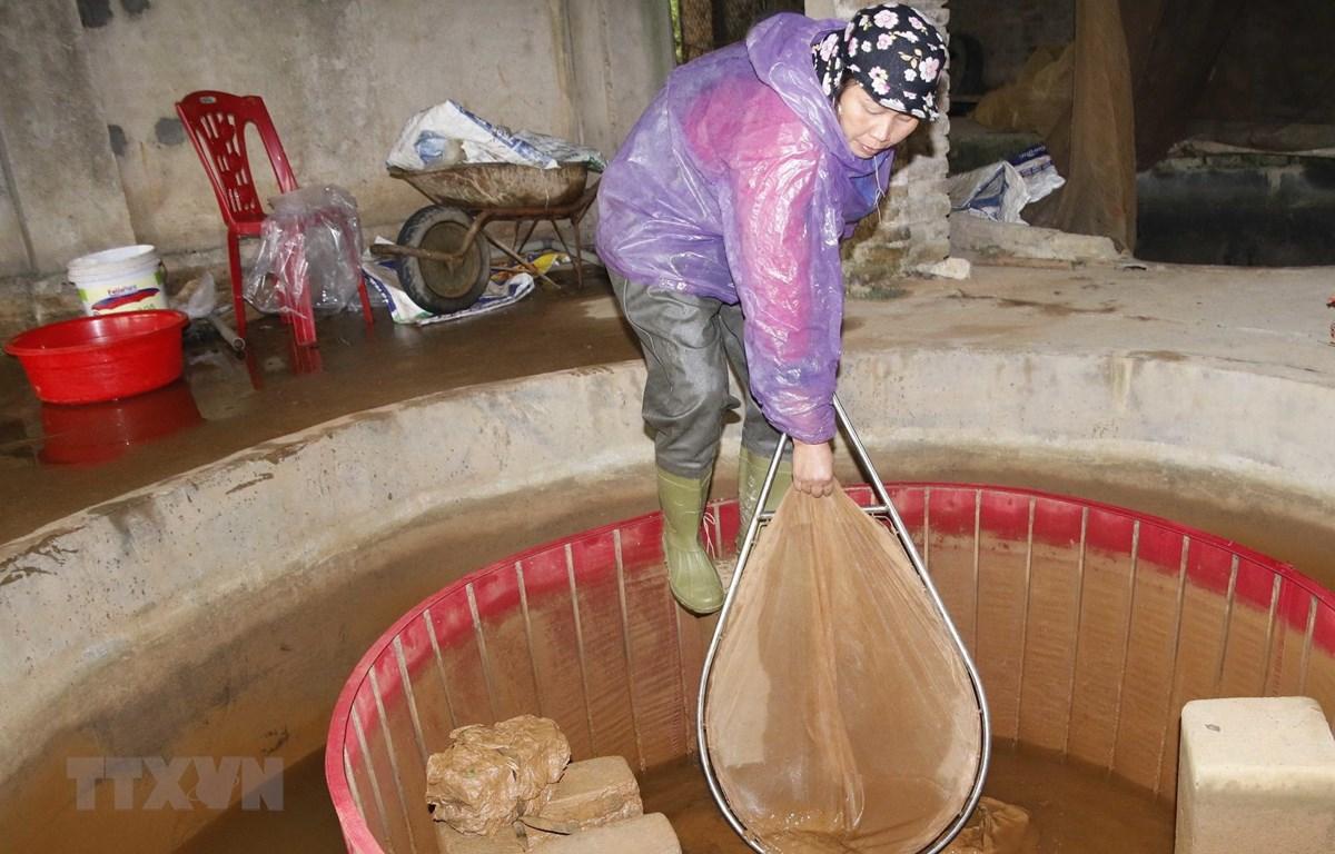 Bể lắng dẫn nước vào ao hồ tụ đầy bùn đỏ. (Ảnh: Quân Trang/TTXVN)