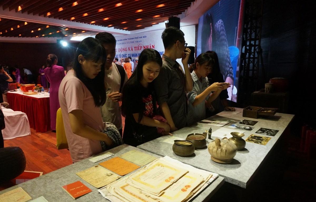 Khách tham quan tìm hiểu các tài liệu, hiện vật tại lễ tiếp nhận của Bảo tàng Hà Nội. (Ảnh: Đinh Thuận/TTXVN)