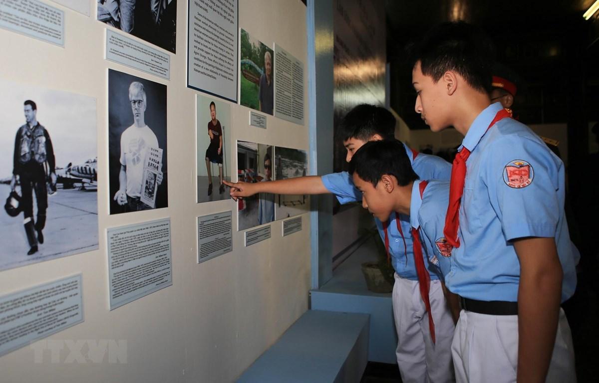 Các em học sinh xem triển lãm. (Ảnh: Hồ Cầu/TTXVN)