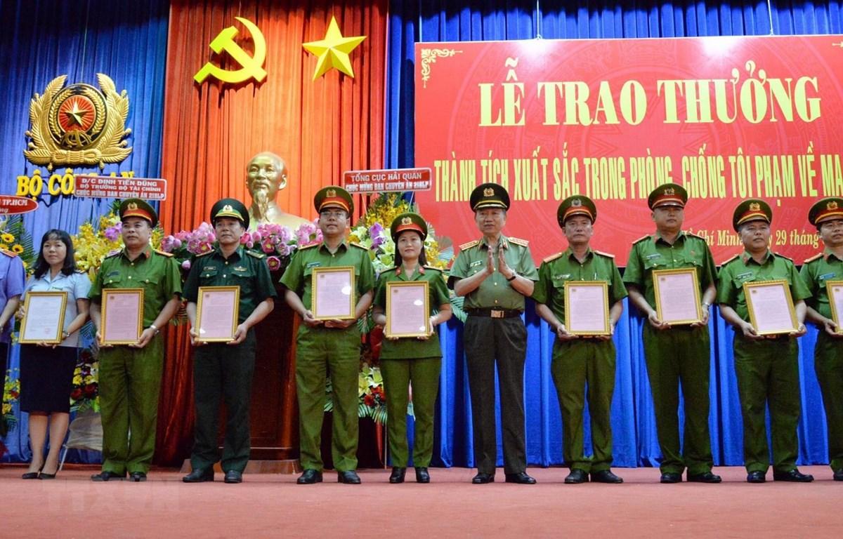 Bộ trưởng Bộ Công an Tô Lâm trao thưởng cho các tập thể có thành tích xuất sắc trong phòng chống tội phạm về ma túy. (Ảnh: Tiến Lực/TTXVN)