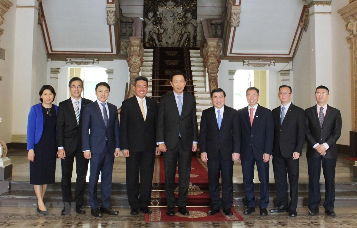 Ông Nguyễn Thành Phong chụp ảnh lưu niệm cùng đoàn nhân sự cấp cao Tập đoàn Keppel. (Ảnh: Gia Thuận/TTXVN)