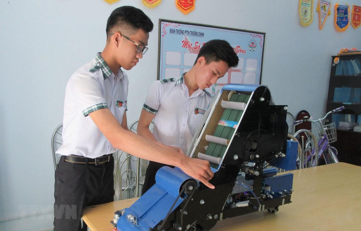 Nguyễn Hữu Thực và Trần Hoàng Nguyên với mô hình máy điều khiển tự động thu gom nông sản. (Ảnh: Nguyễn Thành/TTXVN)