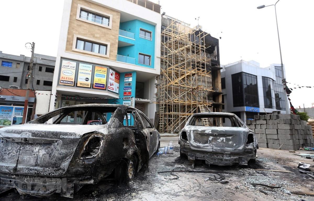 Ôtô bị phá hủy sau một vụ tấn công ở Tripoli, Libya. (Ảnh: AFP/TTXVN)