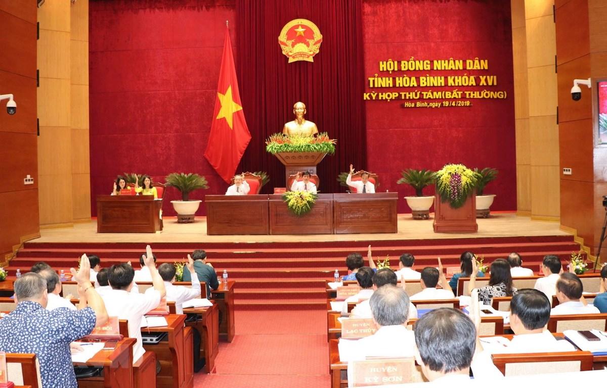 Các đại biểu HĐND tỉnh Hòa Bình thông qua các nghị quyết quan trọng của phiên họp bất thường. (Ảnh: Nhan Sinh/TTXVN)