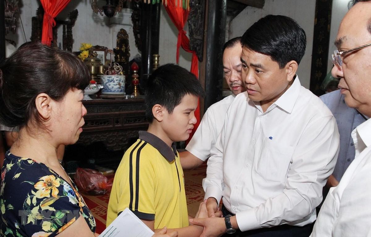 Chủ tịch UBND thành phố Hà Nội Nguyễn Đức Chung thăm hỏi, động viên gia đình chị Lê Thị Thu Hà. (Ảnh: Lâm Khánh/TTXVN)