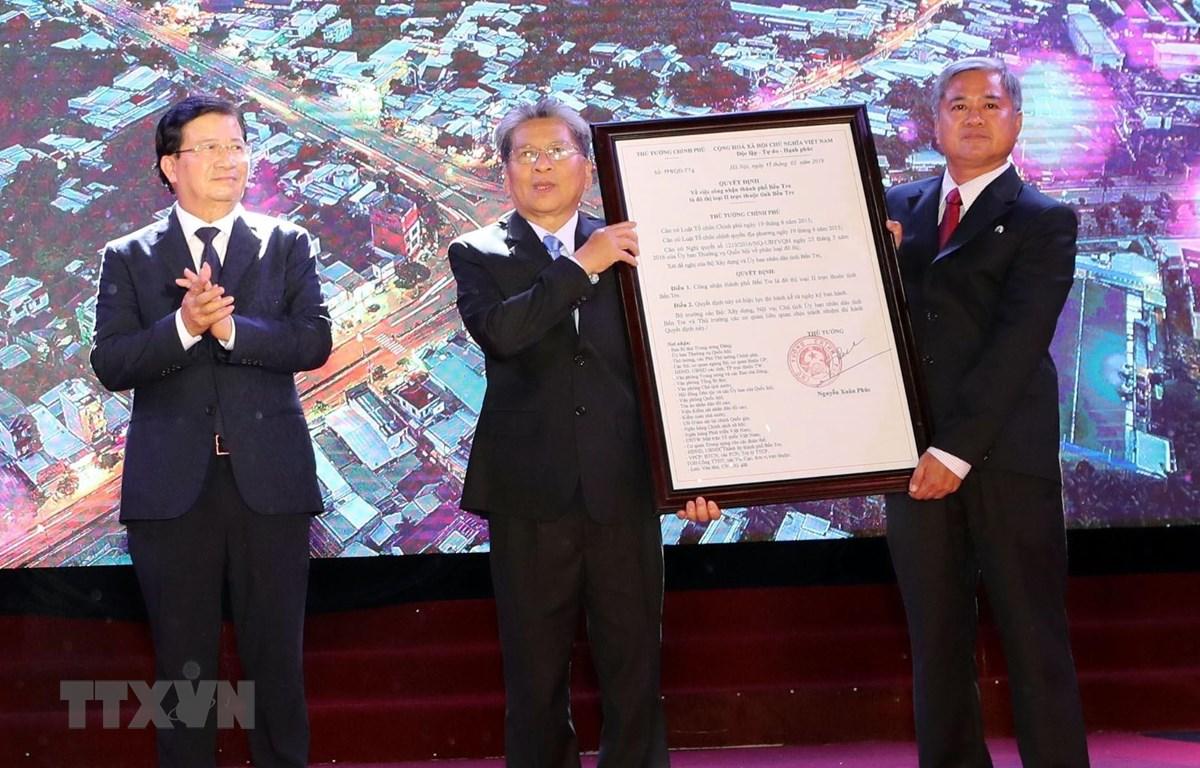 Phó Thủ tướng Trịnh Đình Dũng trao Quyết định của Thủ tướng Chính phủ công nhận thành phố Bến Tre là đô thị loại II trực thuộc tỉnh Bến Tre. (Ảnh: Trọng Đức/TTXVN)