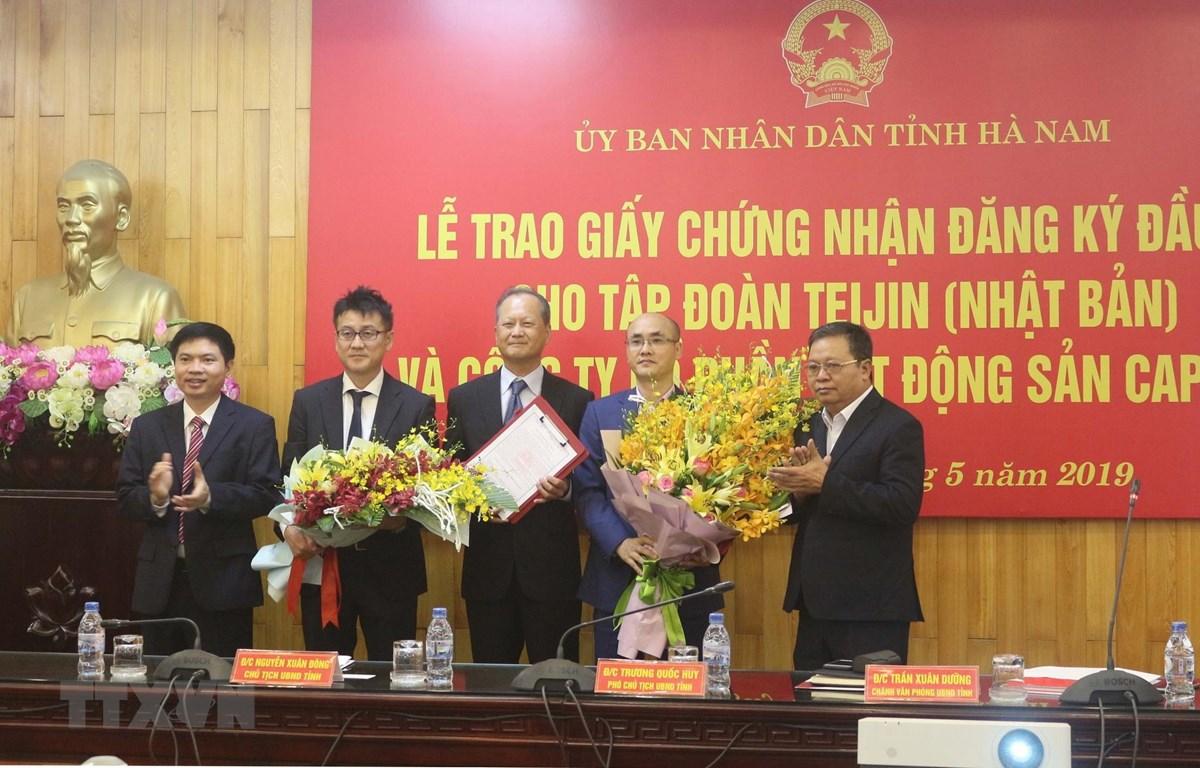 Lãnh đạo tỉnh Hà Nam tặng hoa chúc mừng 2 chủ đầu tư dự án. (Ảnh: Nguyễn Chinh/TTXVN)