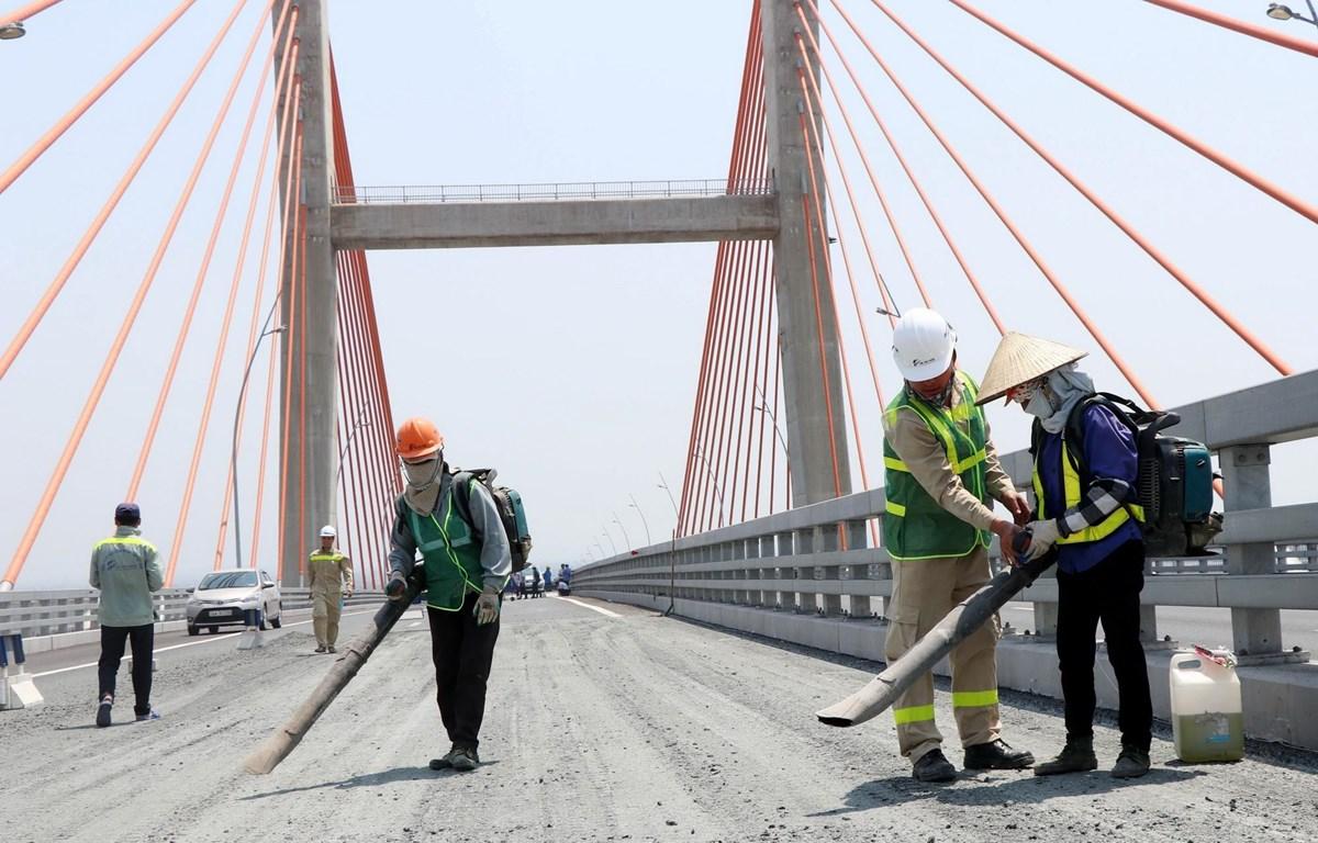 Công nhân vệ sinh mặt đường sau khi cào lớp nhựa cũ. (Ảnh: Văn Đức/TTXVN)