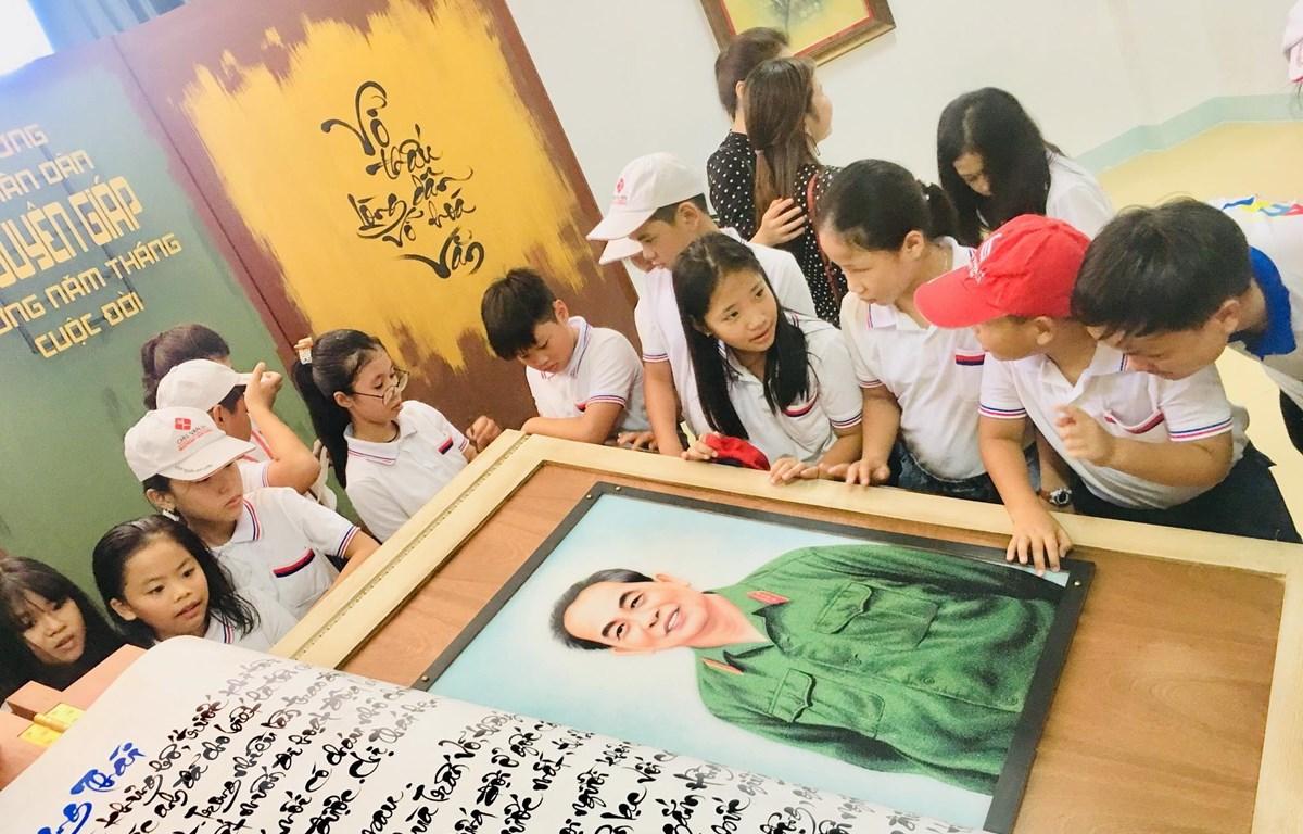 Các em học sinh hào hứng tham quan quyển sách thư pháp viết về Đại tướng Võ Nguyên Giáp. (Ảnh: Võ Dung/TTXVN)