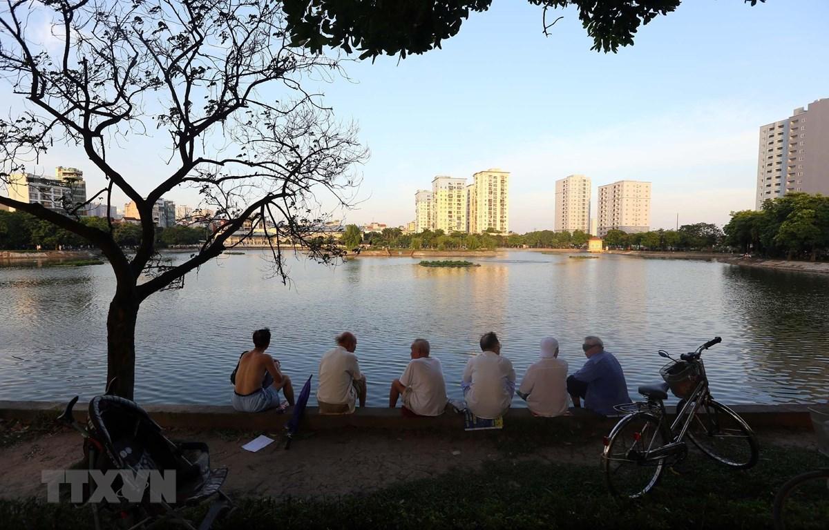 Người dân thủ đô đến các công viên, bờ hồ... hóng mát sau một ngày nắng nóng gay gắt trên 40 độ C. (Ảnh: Danh Lam/TTXVN)
