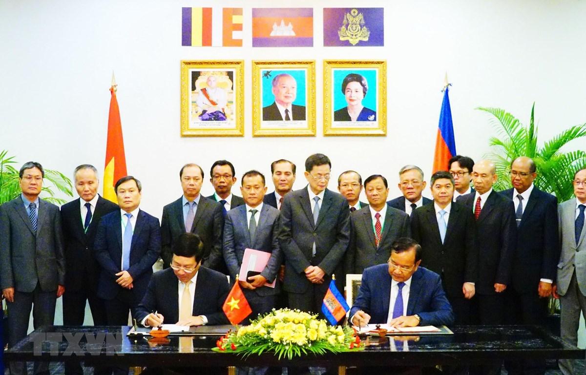 Phó Thủ tướng, Bộ trưởng Ngoại giao Phạm Bình Minh và Phó Thủ tướng, Bộ trưởng Bộ Ngoại giao và Hợp tác quốc tế Campuchia Prak Sokhonn ký kết văn kiện của Kỳ họp. (Ảnh: Minh Hưng/TTXVN)