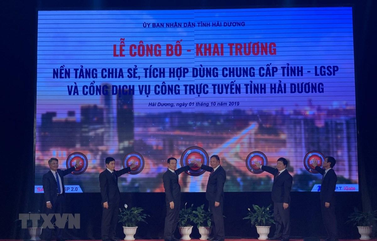 Đại diện các lãnh đạo lên bấm nút Khai trương Nền tảng chia sẻ, tích hợp dùng chung cấp tỉnh - LGSP và Cổng dịch vụ công trực tuyến tỉnh Hải Dương. (Ảnh: Hiền Anh/TTXVN)
