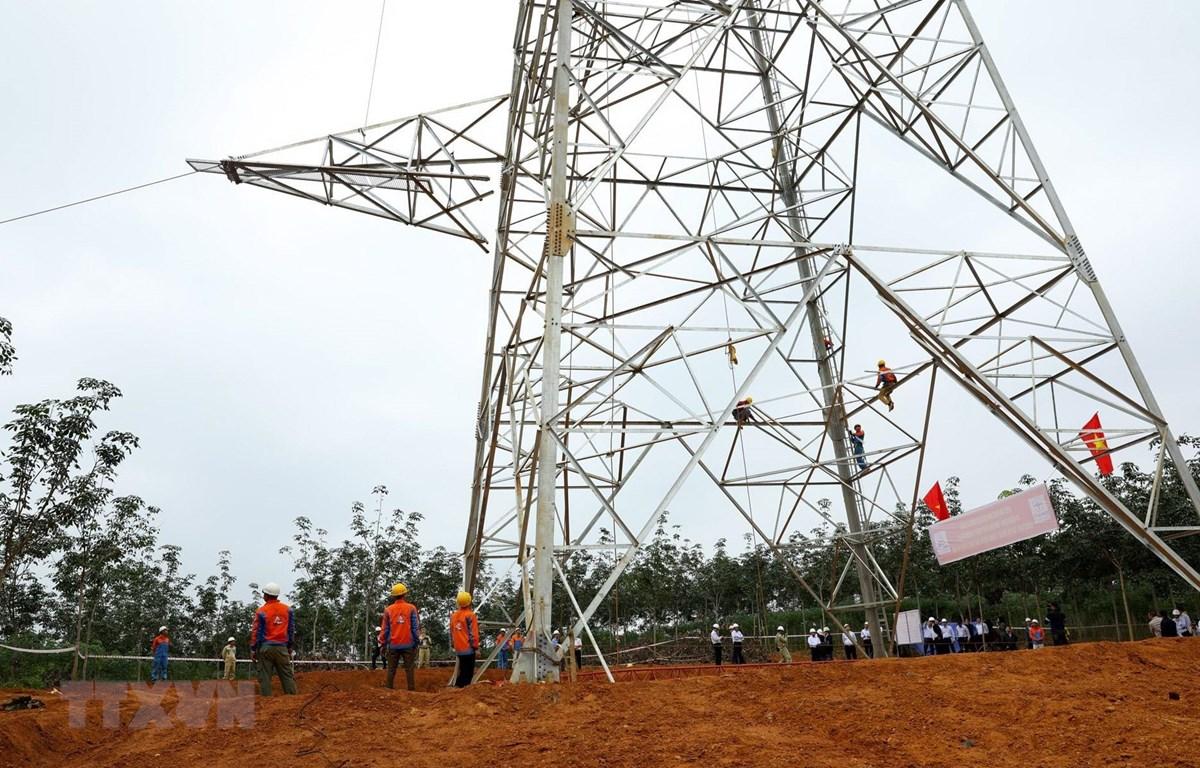 Công nhân Công ty cổ phần Sông Đà 11 thi công lắp đặt thiết bị cột vị trí 158 trên địa bàn huyện Lệ Thủy, tỉnh Quảng Bình. (Ảnh: Ngọc Hà/TTXVN)