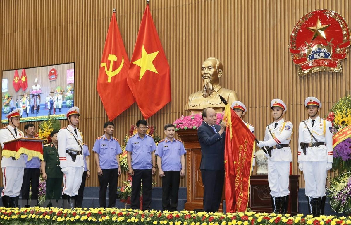 Thủ tướng Nguyễn Xuân Phúc gắn Huân chương Hồ Chí Minh lên lá cờ truyền thống của Viện Kiểm sát Nhân dân Tối cao. (Ảnh: Doãn Tấn/TTXVN)