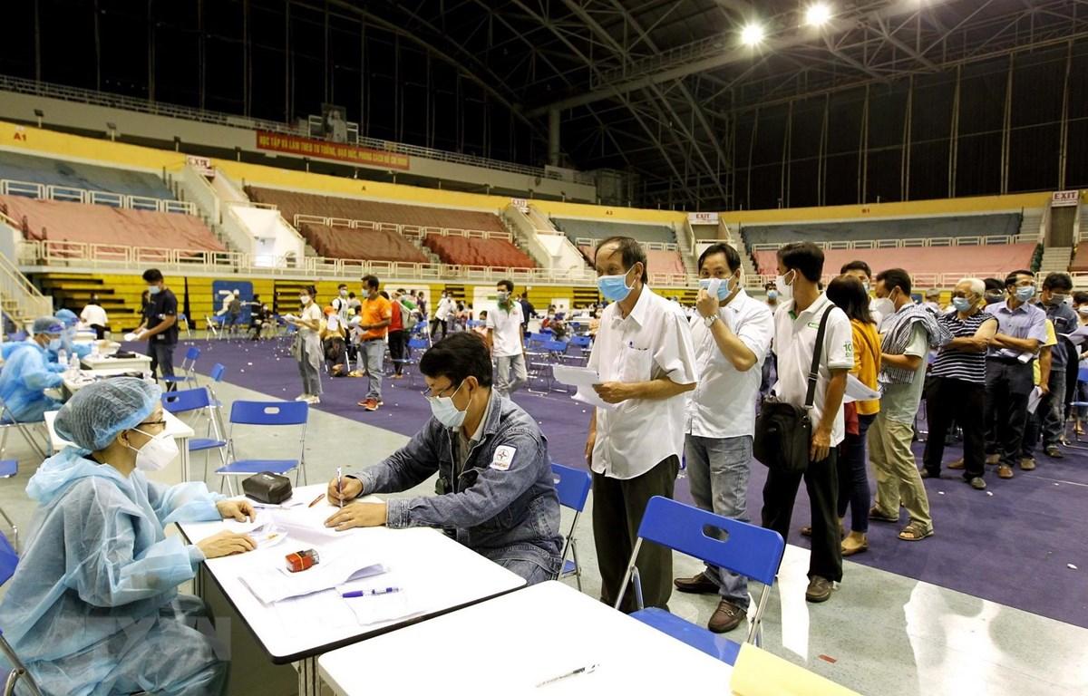 Người lao động xếp hàng chờ thực hiện các thủ tục khai báo y tế trước khi tiêm vaccine phòng COVID-19 tại Nhà thi đấu Phú Thọ. (Ảnh: Thanh Vũ/TTXVN)