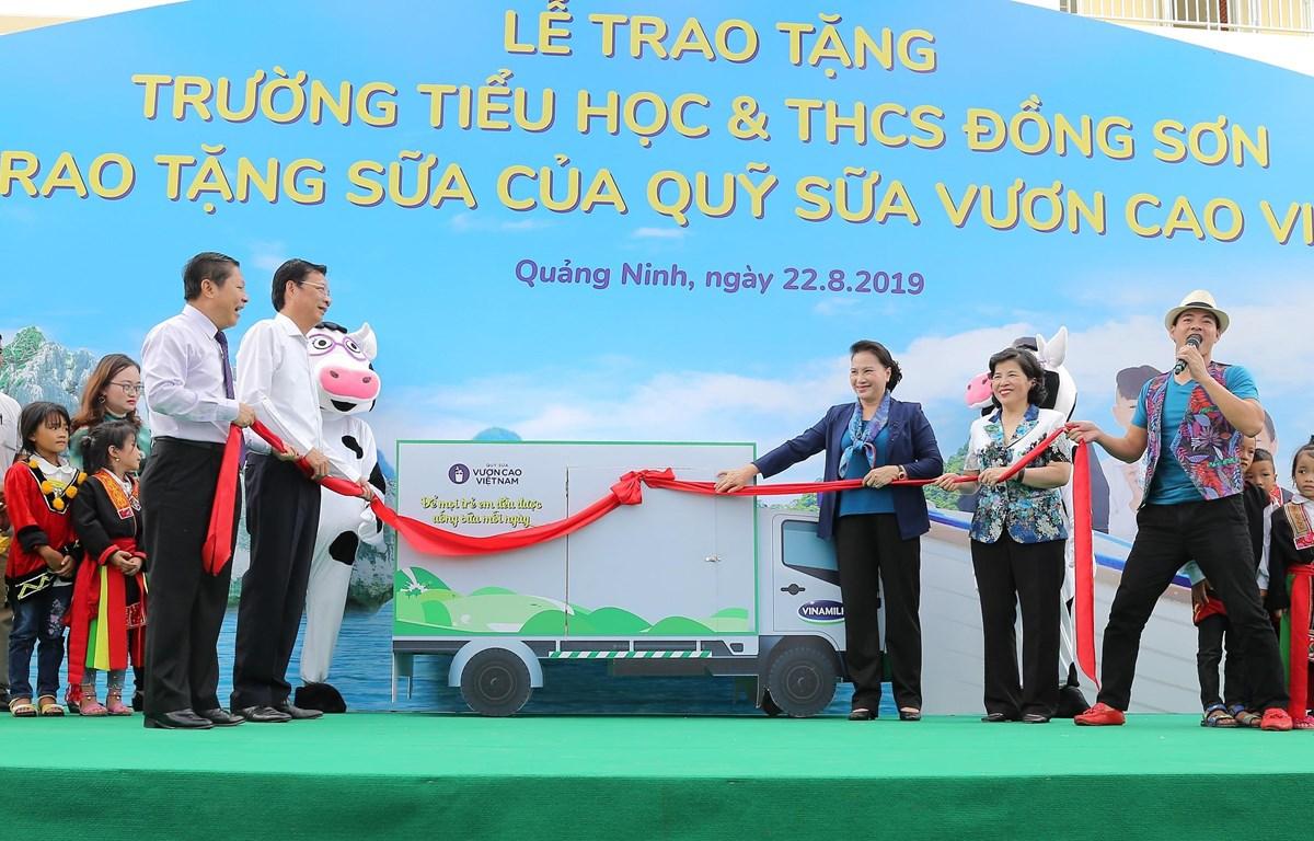 Chủ tịch Quốc hội Nguyễn Thị Kim Ngân cùng các đại biểu và Đại sứ chương trình- Nghệ sĩ Xuân Bắc thực hiện nghi thức mở xe sữa và trao tặng sữa của chương trình Quỹ sữa Vươn cao Việt Nam cho các em học sinh.