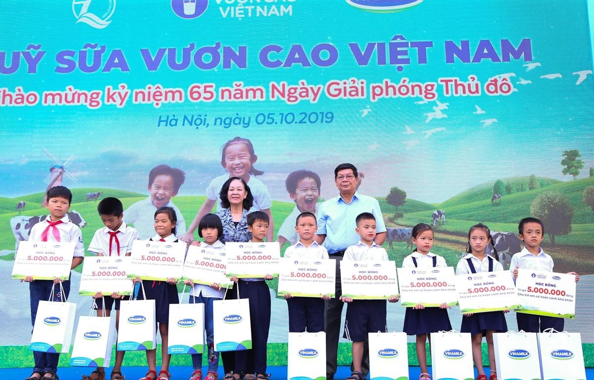 Bà Trương Thị Mai - Ủy viên Bộ Chính trị, Bí thư Trung ương Đảng, Trưởng ban Dân vận Trung ương cùng đại biểu khách mời trao học bổng và sữa của Quỹ Sữa Vươn Cao Việt Nam cho các em học sinh khó khăn có thành tích học tập tốt của trường Tiểu học Tiên Dược
