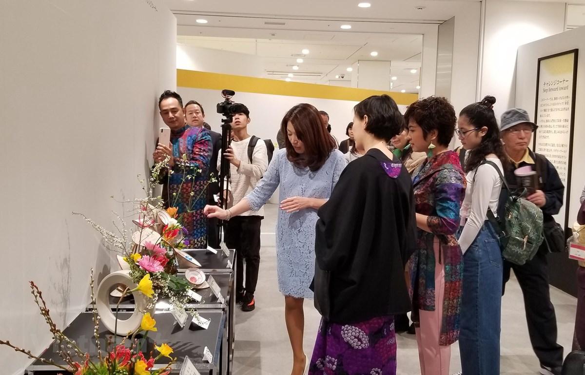 Nghệ nhân Ikenobo Mika, thành viên gia tộc Ikenobo, đang đánh giá các tác phẩm của nghệ nhân Ngọc Linh. (Ảnh: Cẩm Tuyến/Vietnam+)