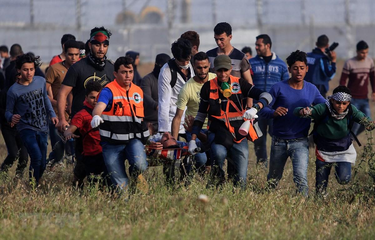 Chuyển người biểu tình Palestine bị thương trong các vụ đụng độ với lực lượng an ninh Israel tại miền Đông Dải Gaza ngày 26/4. (Ảnh: THX/TTXVN)
