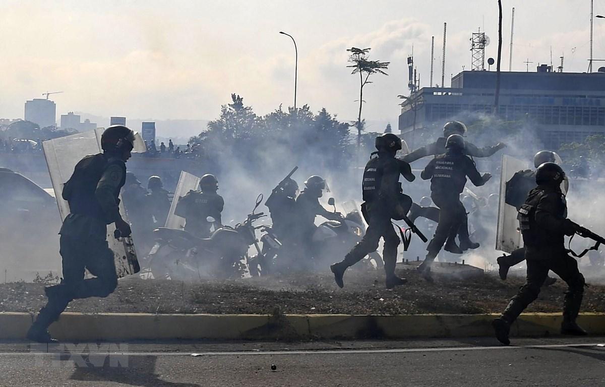 Lực lượng trung thành với Tổng thống Venezuela Nicolas Maduro ngăn các tay súng thuộc nhóm binh sĩ ủng hộ thủ lĩnh đối lập Juan Guaido nổi dậy tại căn cứ quân sự La Carlota ở Caracas ngày 30/4/2019. (Ảnh: AFP/TTXVN)