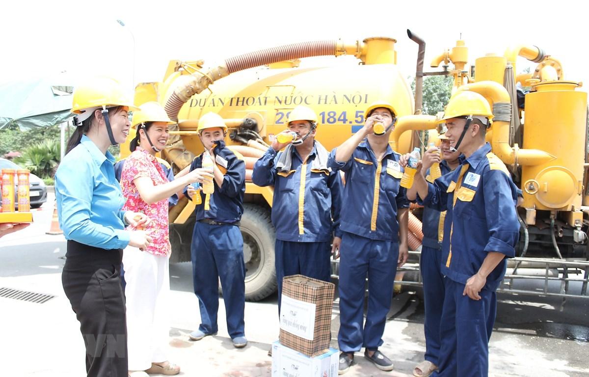 Lãnh đạo Công ty TNHH MTV Thoát nước Hà Nội phát nước uống, động viên người lao động làm việc trong những ngày nắng nóng. (Ảnh: Mạnh Khánh/TTXVN)