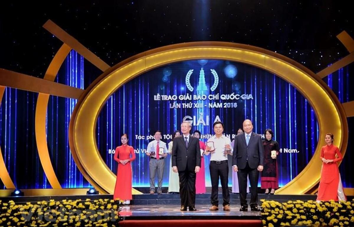Phóng viên Võ Mạnh Hùng (Báo Điện tử VietnamPlus) nhận giải A với tác phẩm Tội ác dưới những tán rừng xanh… Cửa đóng nhưng ruột vẫn rỗng. (Ảnh: Minh Hiếu/Vietnam+)