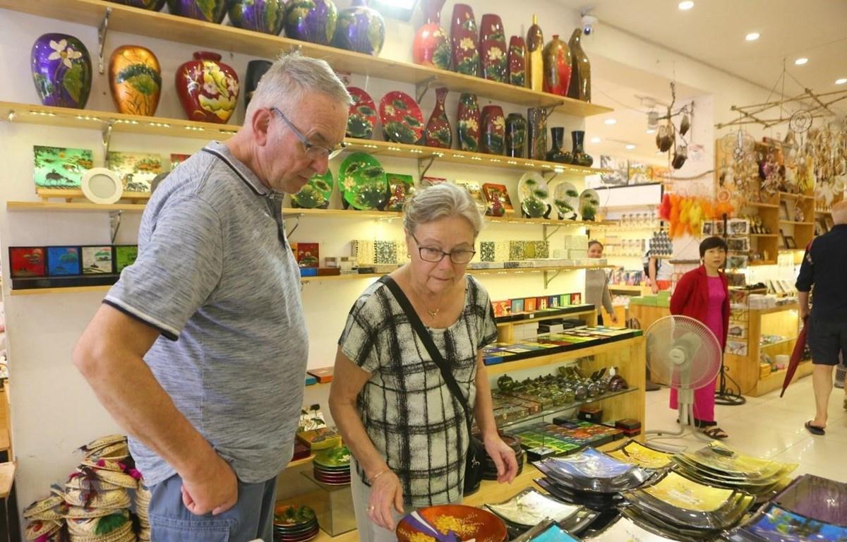 Khách du lịch quốc tế mua các sản phẩm lưu niệm tại Hàng Bông, Hà Nội. (Ảnh: Thành Đạt/TTXVN)