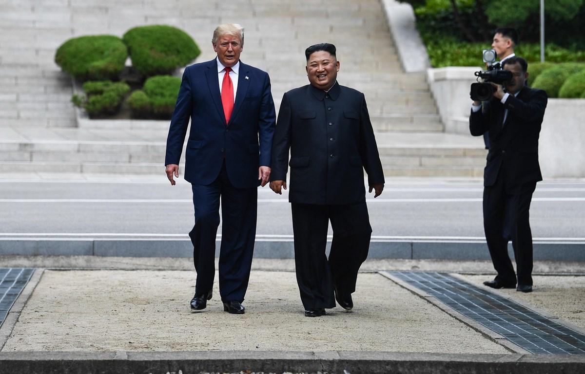 Tổng thống Mỹ Donald Trump (trái) và nhà lãnh đạo Triều Tiên Kim Jong-un (giữa) trong cuộc gặp tại Khu phi quân sự (DMZ) ở biên giới liên Triều chiều 30/6/2019. (Ảnh: AFP/TTXVN)