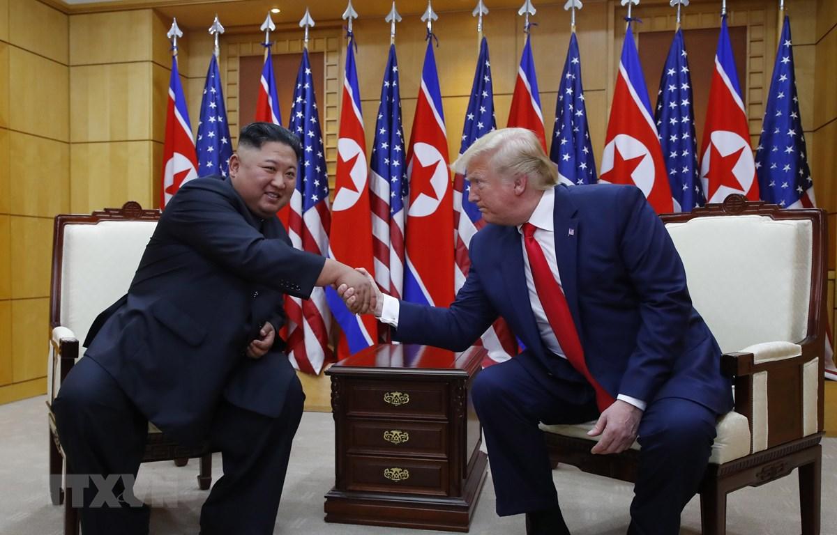 Tổng thống Mỹ Donald Trump (phải) và nhà lãnh đạo Triều Tiên Kim Jong-un trong cuộc gặp ở làng đình chiến Panmunjom tại Khu phi quân sự (DMZ) chiều 30/6/2019. (Ảnh: Yonhap/TTXVN)