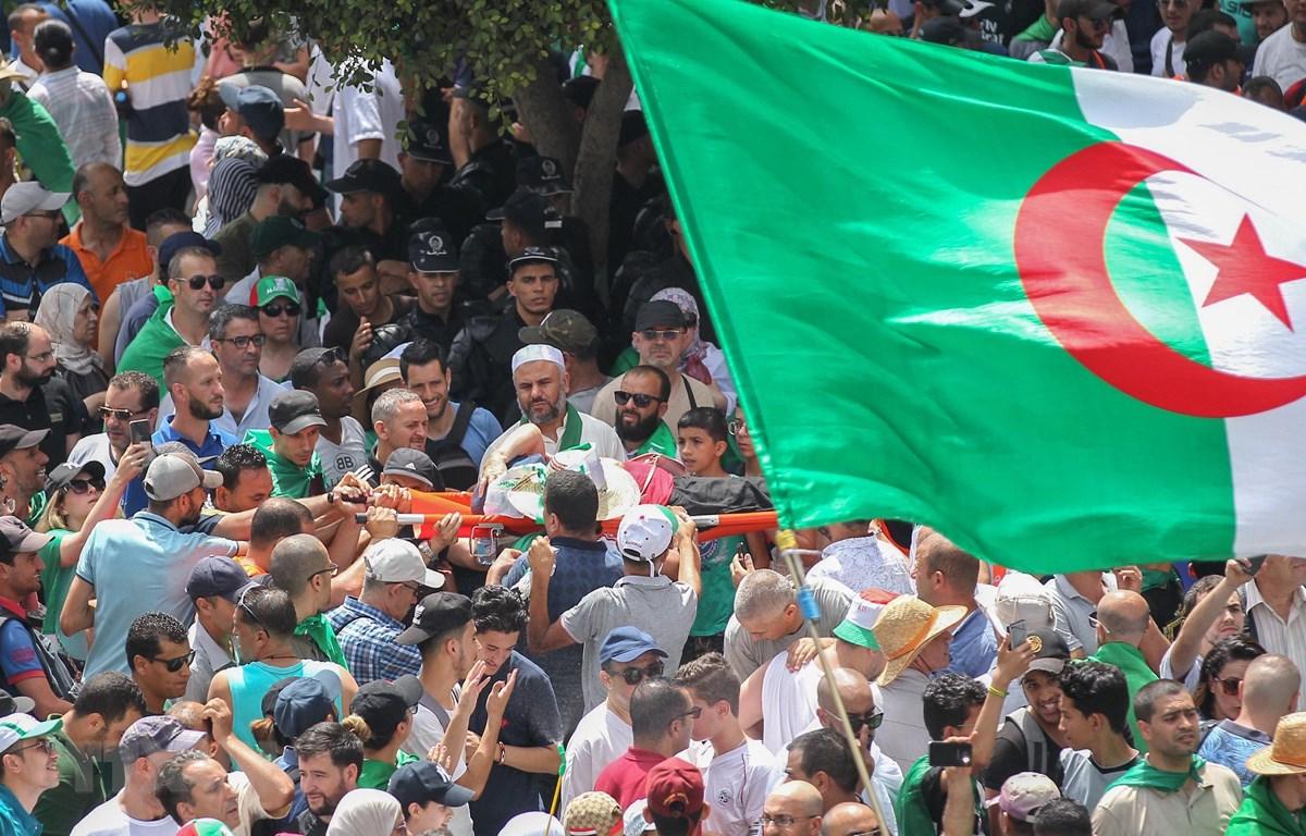 Những người biểu tình mang theo các lá cờ Algeria, đặc biệt là lá cờ khổng lồ ghi tên 48 tỉnh thành nước này, họ vừa hát những bài hát yêu nước để tái khẳng định cam kết không ngừng của họ đối với sự thống nhất, đoàn kết quốc gia và dân tộc. (Ảnh: AFP/TTX