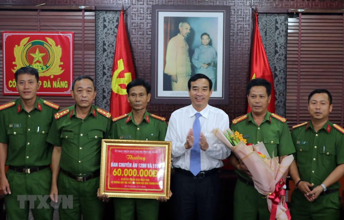 Phó Chủ tịch Ủy ban Nhân dân thành phố Đà Nẵng Lê Trung Chinh trao thưởng cho lực lượng phá án. (Ảnh: Nguyễn Sơn/TTXVN)