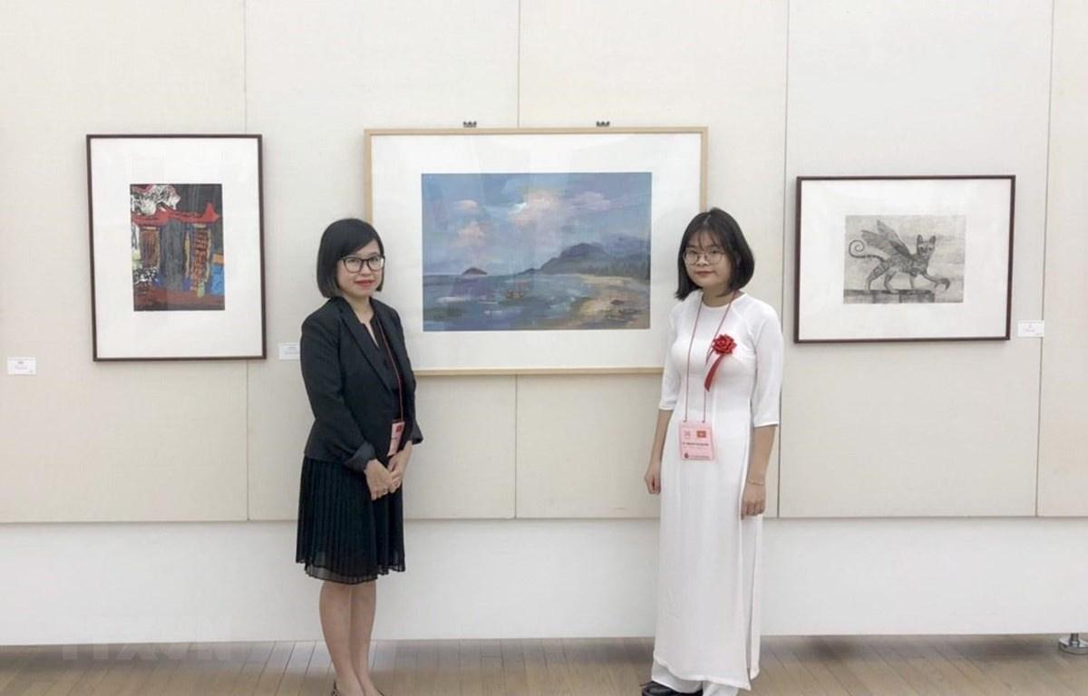 """Vũ Nguyễn Hương Nhi bên bức tranh """"Biển Đêm"""" trưng bày tại Bảo tàng Mỹ thuật quốc gia Nhật Bản..(Ảnh: Thành Hữu/TTXVN)"""