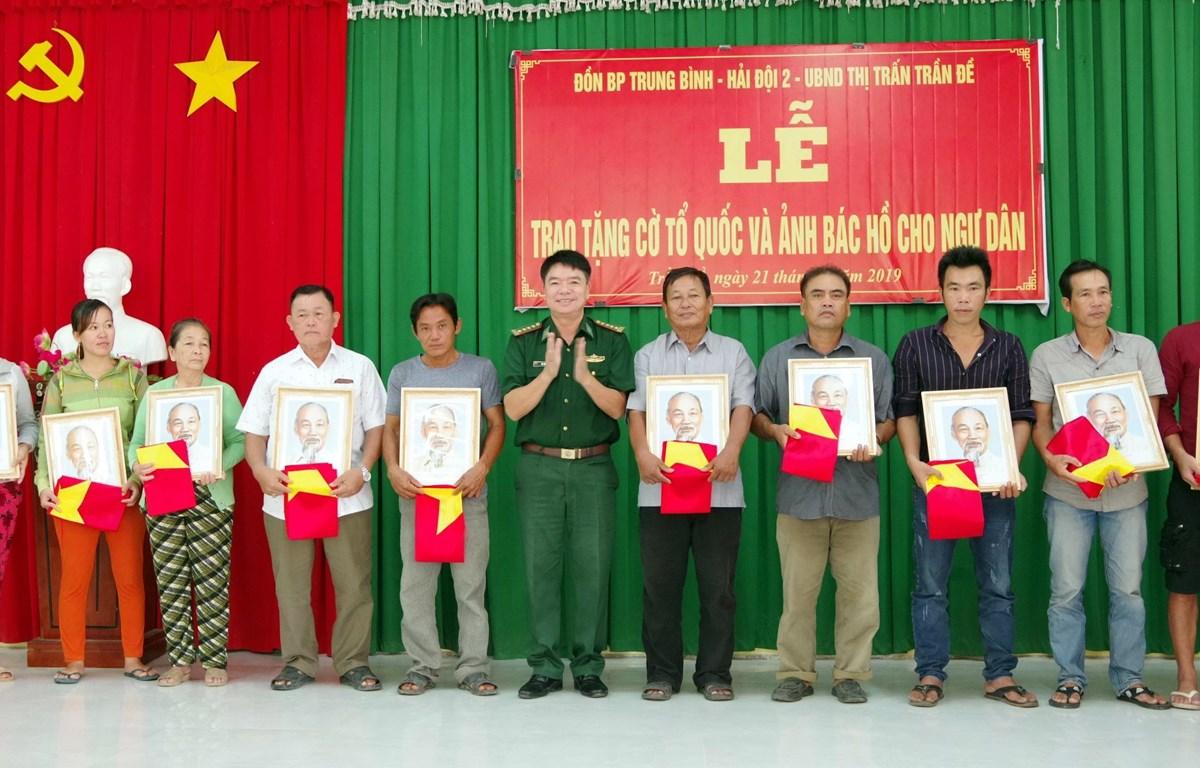 Lãnh đạo bộ đội biên phòng Sóc Trăng trao tặng cờ và ảnh bác Hồ cho ngư dân vùng ven biển Sóc Trăng. (Ảnh: Trung Hiếu-TTXVN)