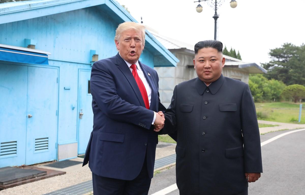 Tổng thống Mỹ Donald Trump (trái) và nhà lãnh đạo Triều Tiên Kim Jong-un trong cuộc gặp tại làng đình chiến Panmunjom ở biên giới liên Triều ngày 30/6/2019. (Ảnh: THX/TTXVN)