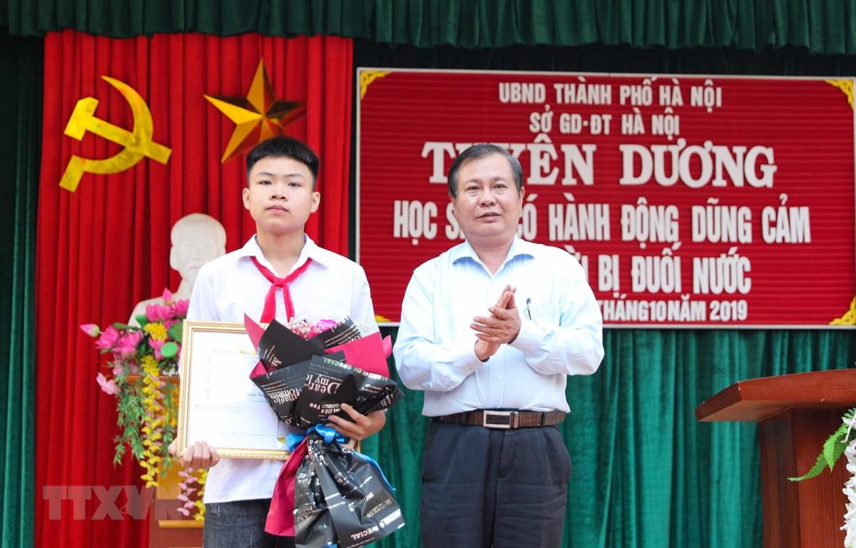 Phó Giám đốc Sở Giáo dục và Đào tạo Hà Nội Lê Ngọc Quang trao Bằng khen của Chủ tịch Ủy ban Nhân dân thành phố Hà Nội cho em Phan Trung Hiếu. (Ảnh: Thanh Tùng/TTXVN)