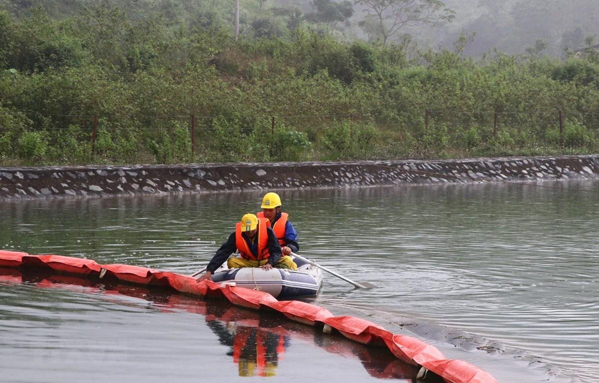 Lực lượng chức năng kiểm tra phao ngăn dầu tại Nhà máy nước sông Đà. (Ảnh: Thanh Hải/TTXVN)